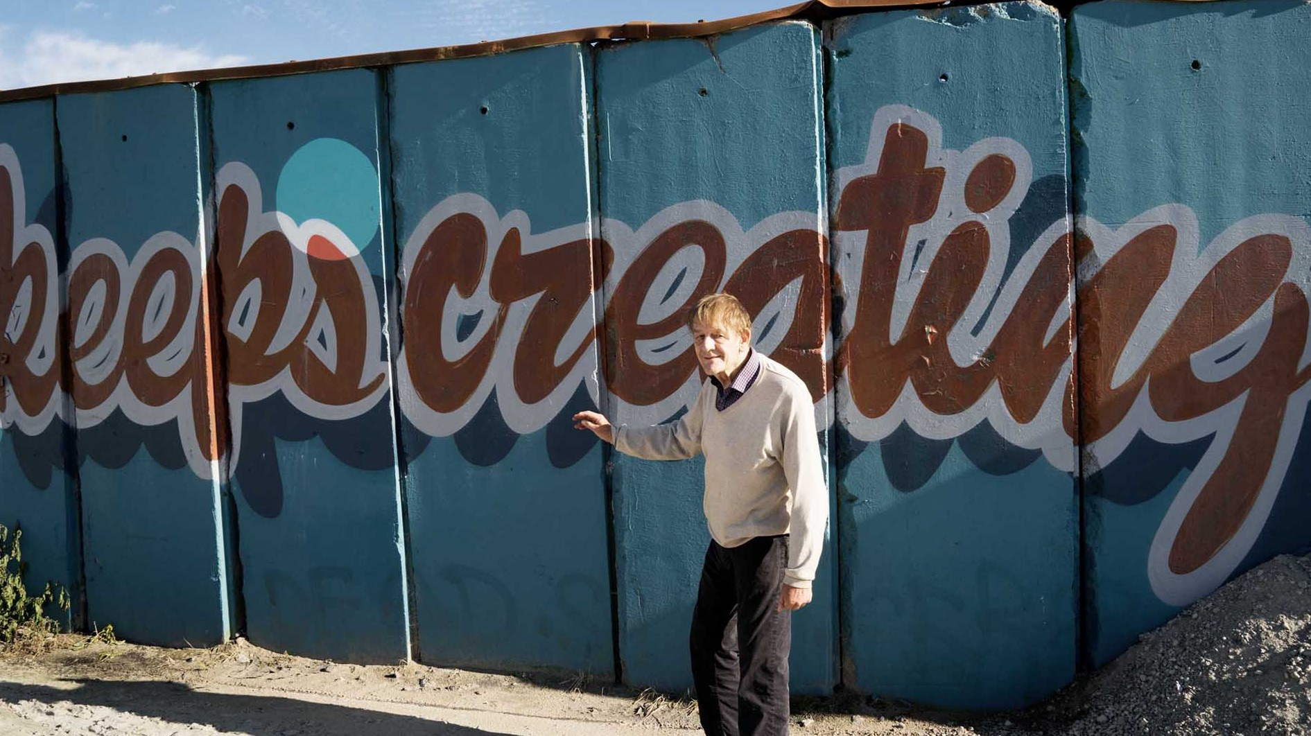Per Nørgård in front of a mural reading 'keeps creating'